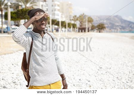 Trendy Dark-skinned Male In Fashionable Clothes Having Backpack Holding Hand On Forehead Looking Int