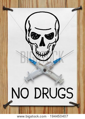 Banner with a skull and needles nailed to a wooden wall. The concept of drug addiction