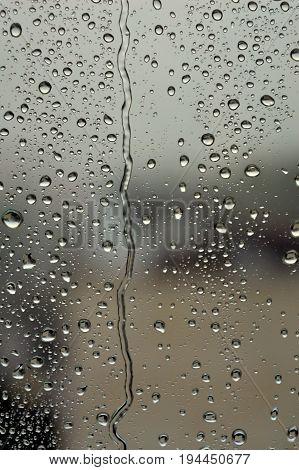 Drops of rain on the window rainy day dark tone. Shallow DOF