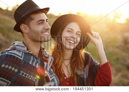 Romantic Female And Male In Black Hats Sitting At Sunrise On Field Smiling Pleasantly Being Happy To