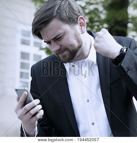 Nervous man swearing into his mobile phone. The bad news negative emotions concept.