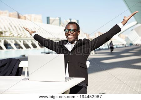 Happy Black Businessman Raising His Hands With Joy Being Glad To Sign Profitable Contract With Busin