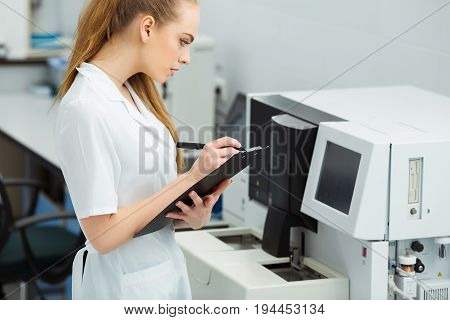 Attractive female lab worker making medical research in modern laboratory. Scientist holding documents folder with analysis results