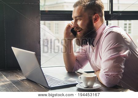 Portrait of a young bearded businessman working with laptop (Success knowledge victory money)