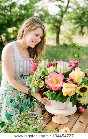 hobby, work, floral design, wedding, celebration concept - pretty smiling woman in summer dress with green print and with light makeup arranging roses, peonies and dianthuses in great bouquet