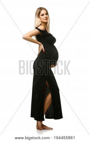 Beautiful pregnant young woman in long black dress. Studio portrait isolated on white background. Copy space.