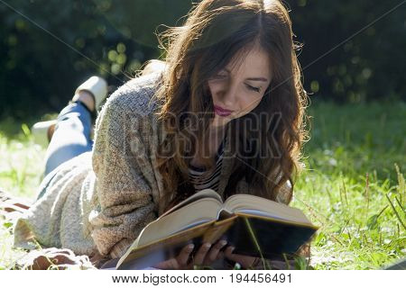 Beautiful young woman reading a book outdors. (relax romance poetry rest)