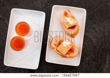 An overhead photo of Spanish tapas in a modern bar. Two shots of gazpacho, cold tomato soup, and pinchos of tortilla, Spanish omelette, on slices of bread, on a dark black table with a place for text