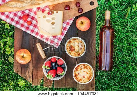Overhead photo of picnic with apples, bottle of rose wine, fresh fruit in plastic container, piece of Dutch cheese, and a baguette, on a rustic wooden board on top of green grass, with place for text