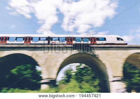 Geneva Switzerland - June 25 2017: Swiss regional train passing over a bridge in the Geneva Canton region with motion blur.