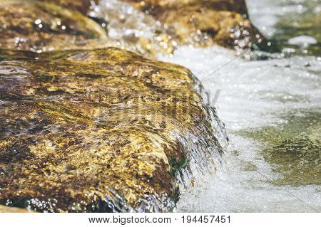 Small waterfall in a torrent with shallow depth of field
