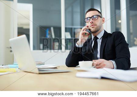 Elegant broker calling on smartphone in office