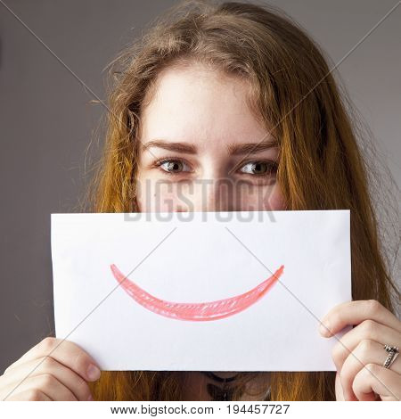 Woman showing a blank paper with a smile and happy emotion as a symbol of the false mask of joy and happiness. The psychological portrait body language gestures facial expressions concept.
