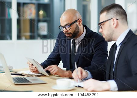 Two men in suits learning financial statistics in touchpad