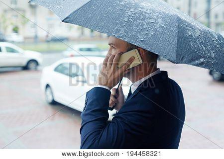 Broker under umbrella phoning in the street