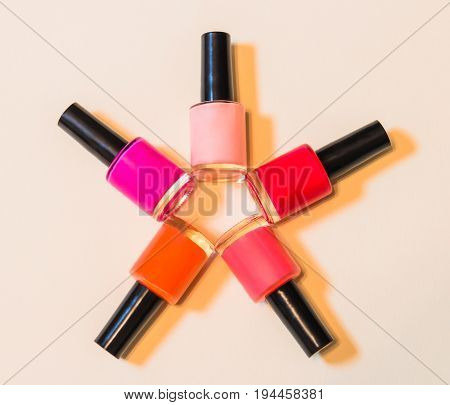Group of nail polishes on beige background