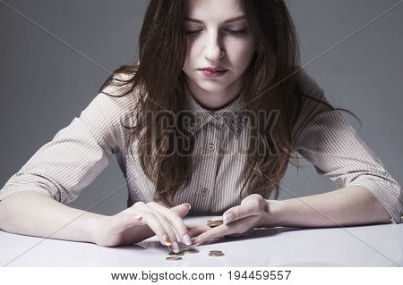 Family debts. Young frustrated and desperate Woman counting small money (Bankrupt poverty tax money concept)