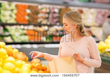 sale, shopping, food, pregnancy and people concept - happy pregnant woman buying oranges and putting them into paper bag at grocery store or supermarket