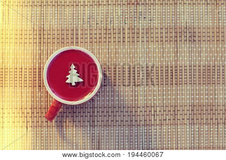 Inverted red cup with a Christmas tree symbol on a table background top view / Holiday wishes from the other side