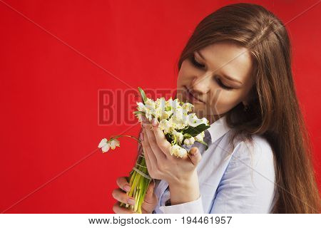 Close-up portrait of Beautiful young woman enjoying nature. Happy female smell a flower with close eyes on red background. (Pleasure nature travel vacation)