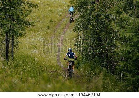 men athletes mountain biking on forest trail