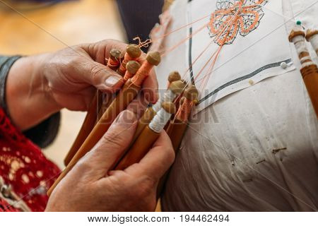 Needlework concept, old craft woman makes bobbin lacing or Palickovanie - Folk art, hobby, hand made product creating