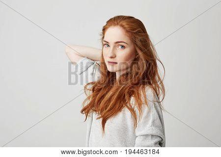 Portrait of young pretty ginger girl with freckles looking at camera touching hair over white background. Copy space.