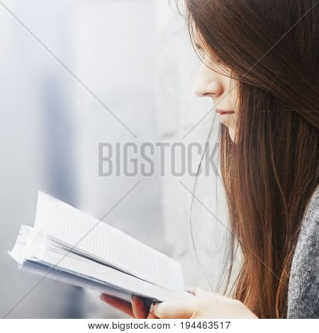 Young beautiful woman enjoying reading interesting books in old center of europe city (Knowledge development education success youth concept)