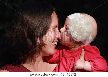Parents love. B beautiful little baby girl kissing her mother. (The family security childhood concept)