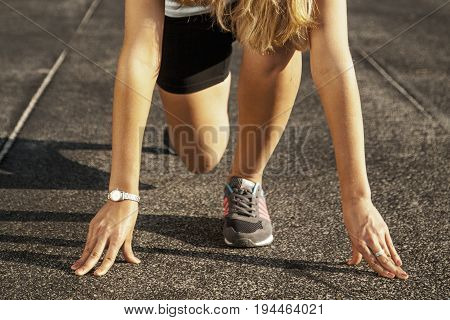 Beautiful athlete woman on a race track is ready to run (Sports healthy lifestyle health willpower concept)
