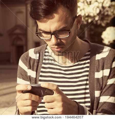 Social Media addiction. young man holding a smartphone(psychological problems media mania concept)