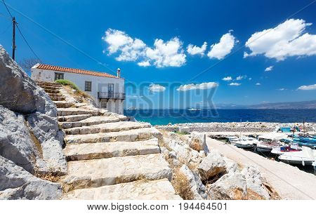 Travel Greece. View from Hydra Island. Traditional Greek house. Castello Hydra and Kamini beach. Blue sky with soft white clouds