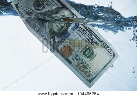 Money concept showing US Dollar sinking in water as a symbol of global economic crisis