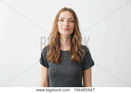 Portrait of young pretty positive girl smiling looking at camera over white background. Copy space.