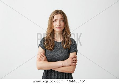 Portrait of young pretty girl looking at camera with contempt over white background. Crossed arms. Copy space.