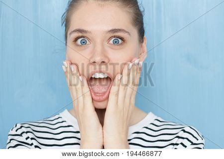 Cute Young Caucasian Female In Navy Striped T-shirt With Opening Mouth Widely, Saying Omg, Wow, Havi
