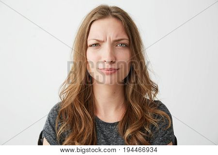 Portrait of displeased young pretty girl looking at camera with contempt over white background. Copy space.