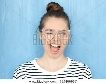 Close Up Portrait Of A Happy Young Hipster European Teen Girl In Nerdy Square Glasses Blinking At Ca