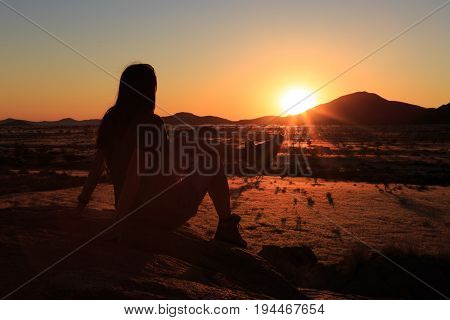 Lonely Girl Watching The Sunset At African Savanna Landscape. Namibia, South Of Africa.