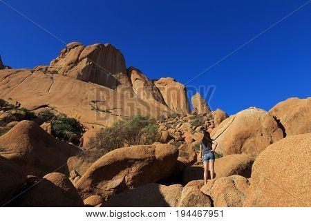 Girl at Spitzkoppe aka Sptizkop - unique rock formation in Damaraland landscape Namibia Africa.