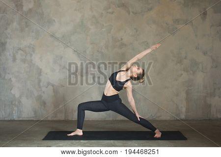 Young Woman Practicing Yoga Warrior Pose, Virabhadrasana Against Texturized Wall / Urban Background
