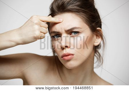 Young brunette girl displeased of her problem acne face skin over white background. Health cosmetology and skincare. Copy space.