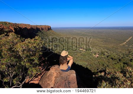 Girl Sitting On Stone On The Cliff At An African Landscape. Waterberg Plateau, Namibia