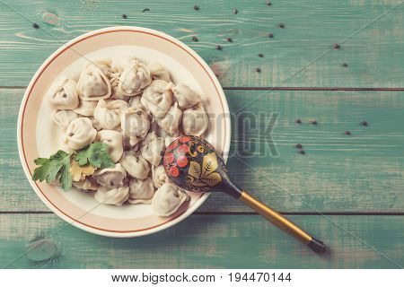 Homemade Meat Dumplings russian pelmeni with laurel leaf parsley on plate and green wooden background with pepper and old russian wooden spoon. Top view and toned image with free space.