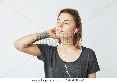 Portrait of young tender girl listening music in headphones with closed eyes over white background. Copy space.