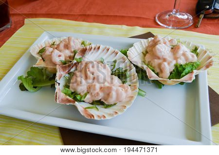 Cocktail of pink shrimp served in scallops in the dolomites in Italy