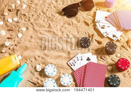 Beachpoker. Chips and cards on the sand. Around the seashells, sunglasses and suntan cream. Top view. Copy space. Flat lay. Sun flare