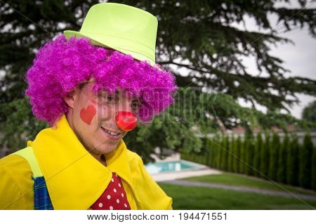Portrait of the red nose clown with green hat and big red tie