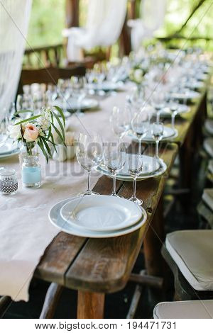 Glasses and plates on the festive wooden table. Wedding table decor concept. Table setting in classic style, setout. fine art.