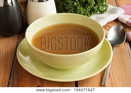 Bone broth made from beef served in a green soup bowl